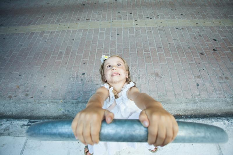 Het glimlachen Kindmeisje het spelen dichtbij met weg in de stad stock foto