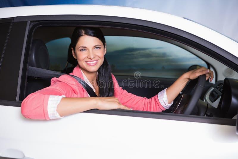 Het glimlachen klantenzitting bij het wiel van een auto voor verkoop stock fotografie