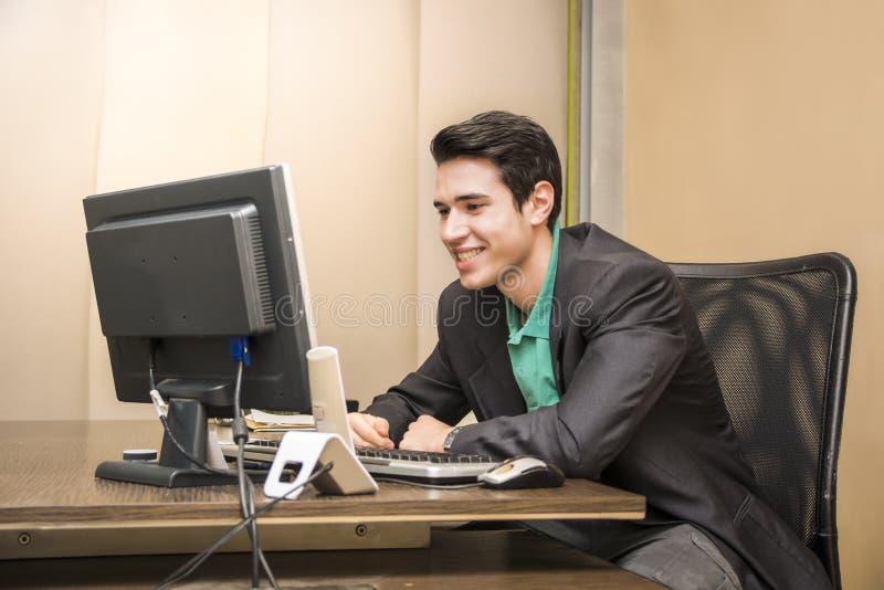 Het glimlachen knappe jonge zakenmanzitting bij bureau in bureau stock fotografie