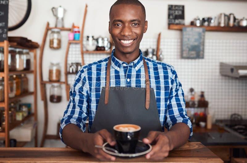 Het glimlachen koffiebarista die een verse kop van cappuccino houden royalty-vrije stock afbeelding