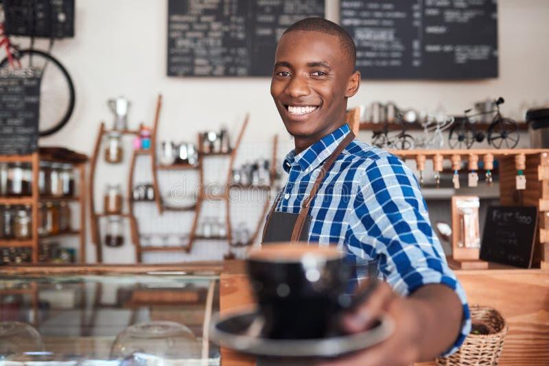 Het glimlachen koffiebarista die omhoog een verse kop van cappuccino aanbieden royalty-vrije stock foto's