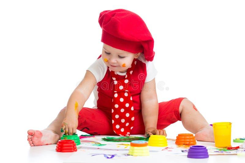 Het glimlachen kunstenaarskind het schilderen door vingers stock afbeelding