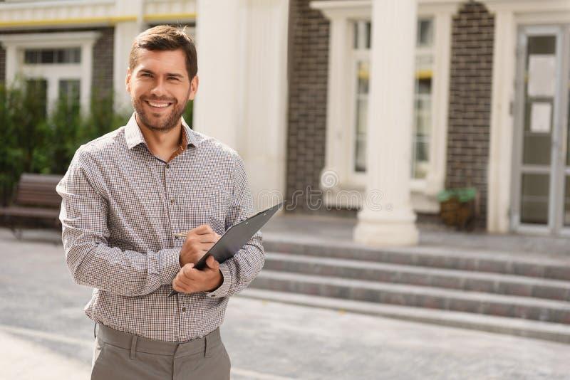 Het glimlachen makelaar in onroerend goed die zich buiten modern huis bevinden stock foto's