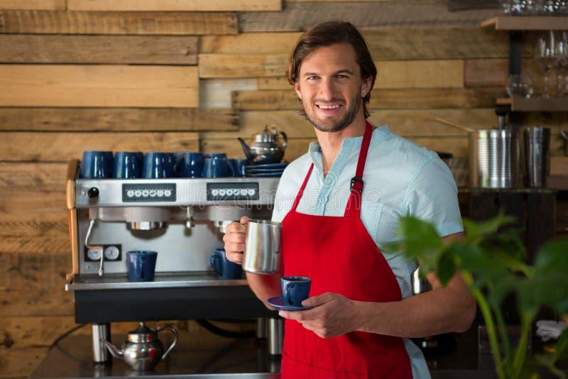 Het glimlachen mannelijke barista die koffie in koffie maken stock afbeeldingen