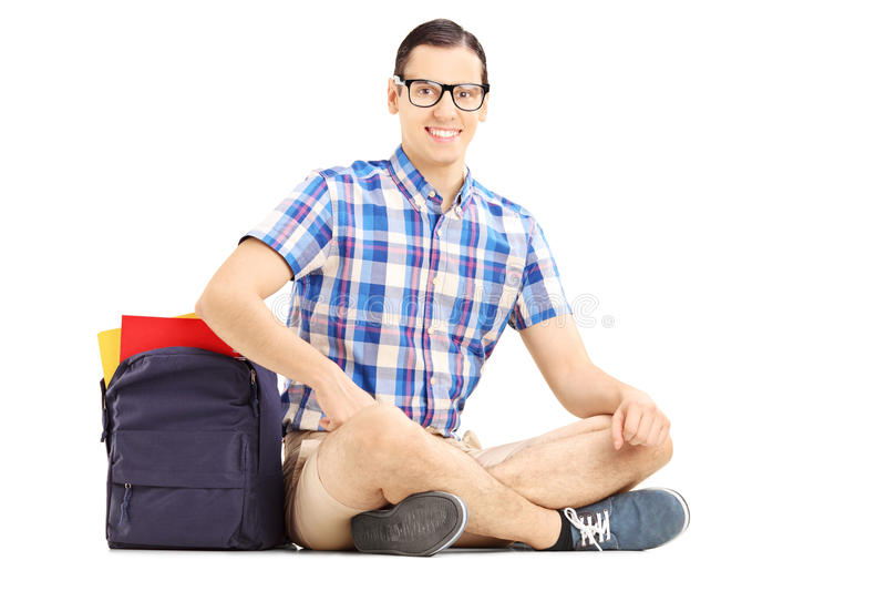 Het glimlachen mannelijke studentenzitting op een vloer met zak en boeken stock afbeelding