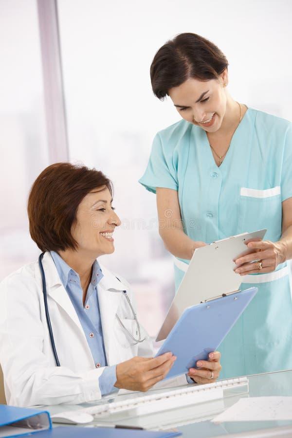 Het glimlachen medische deskundigheid die met medewerker werkt royalty-vrije stock afbeeldingen