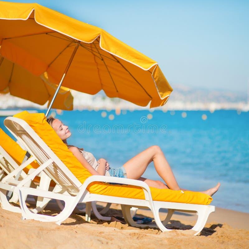 Het glimlachen meisje het ontspannen op een strand royalty-vrije stock afbeeldingen