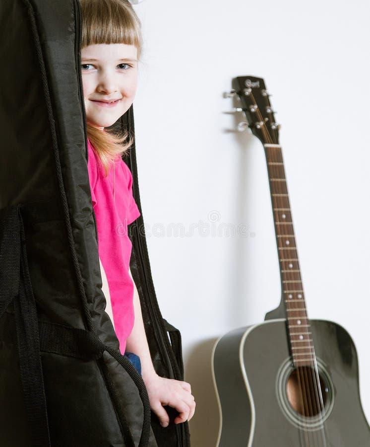 Het glimlachen meisje het verbergen in de dekking van een gitaar royalty-vrije stock afbeeldingen