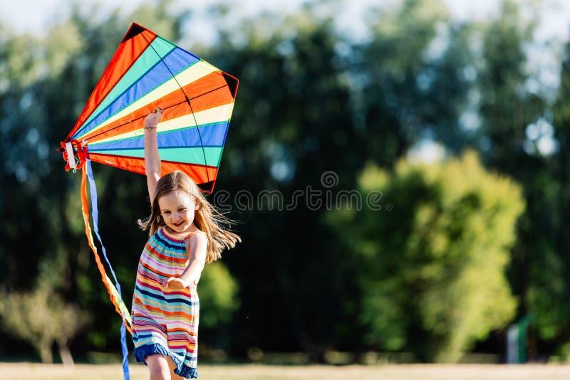 Het glimlachen meisje het spelen met een kleurrijke vlieger in het park royalty-vrije stock fotografie