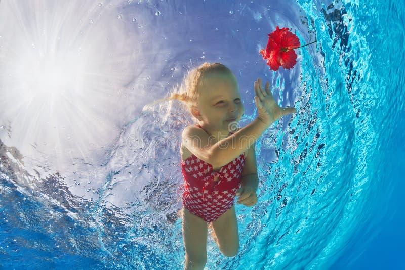 Het glimlachen meisje zwemmen onderwater in pool voor tropische rode bloem stock fotografie