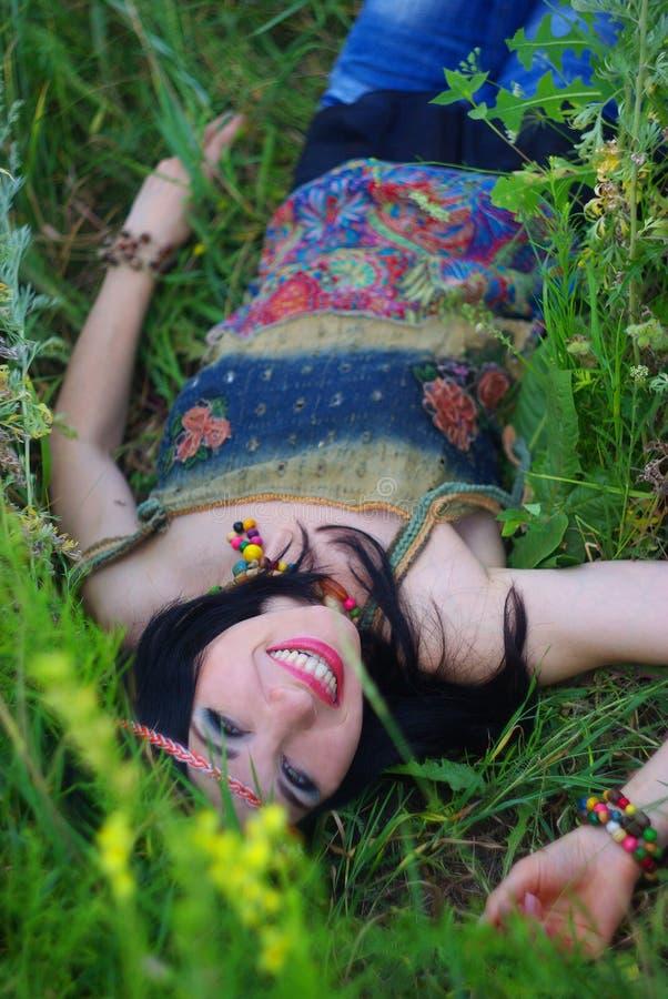 Het glimlachen meisjeshippie die in het gras en de bloemen liggen Bohostijl, royalty-vrije stock foto