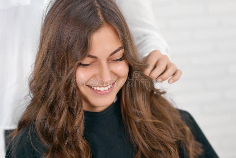 Het glimlachen meisjeszitting in beaty salon, wachten voor kapsel stock foto's