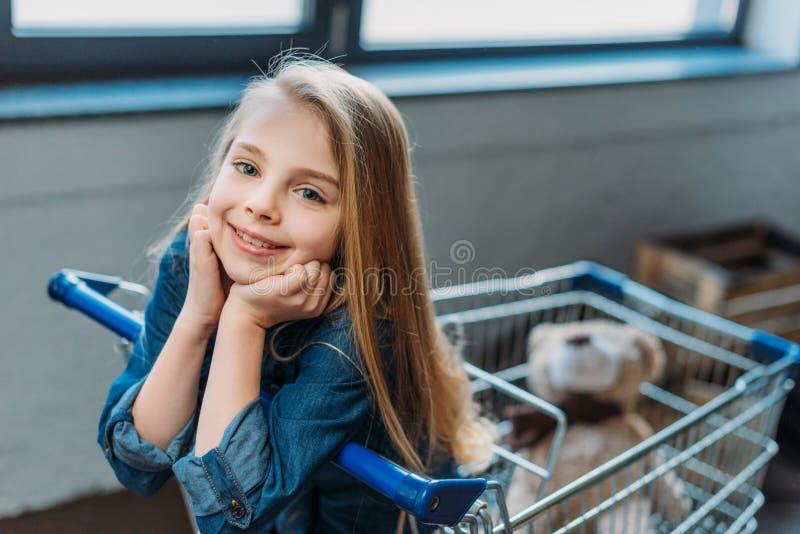 Het glimlachen meisjeszitting in boodschappenwagentje stock fotografie