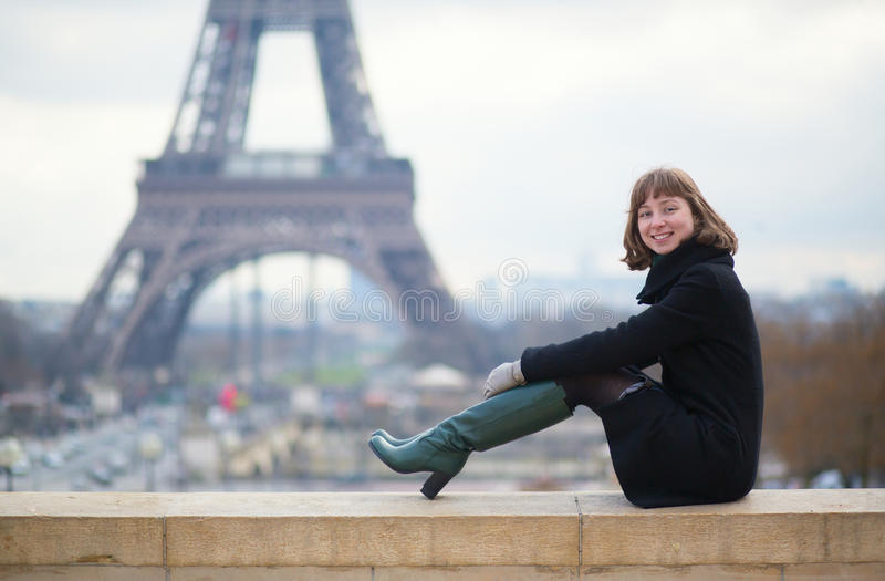 Het glimlachen meisjeszitting dichtbij de toren van Eiffel royalty-vrije stock afbeelding