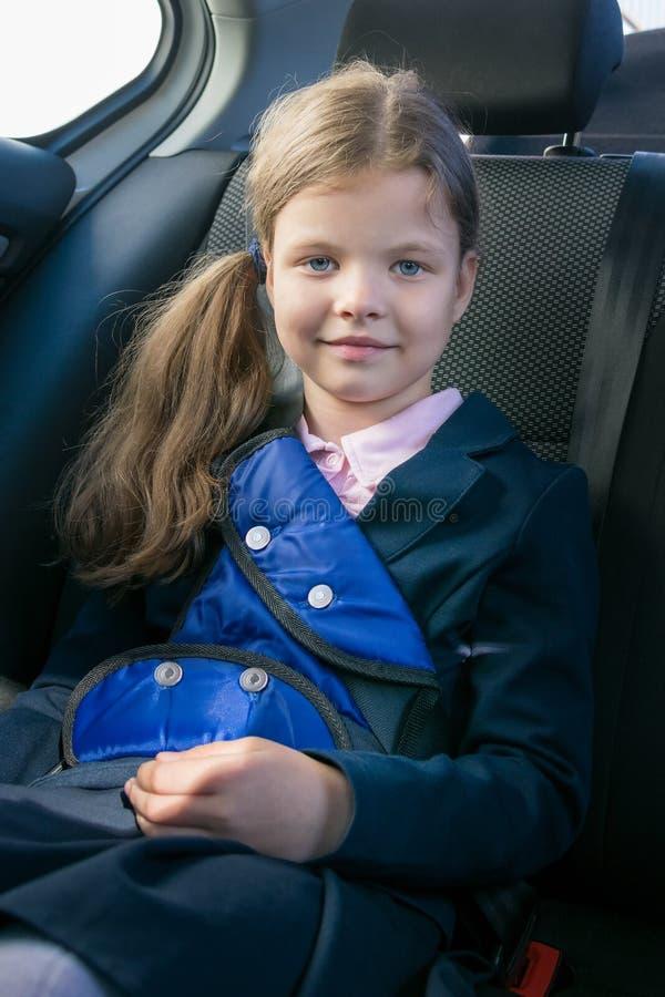 Het glimlachen meisjeszitting in een auto die een veiligheidsgordel in een kindzetel dragen royalty-vrije stock foto