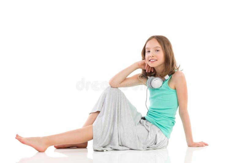 Het glimlachen meisjeszitting met hoofdtelefoons op haar hals stock foto