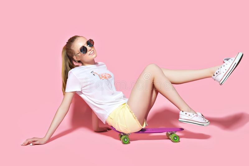 Het glimlachen meisjeszitting op skateboard royalty-vrije stock foto