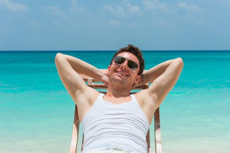 Het glimlachen mens het ontspannen op strand stock fotografie
