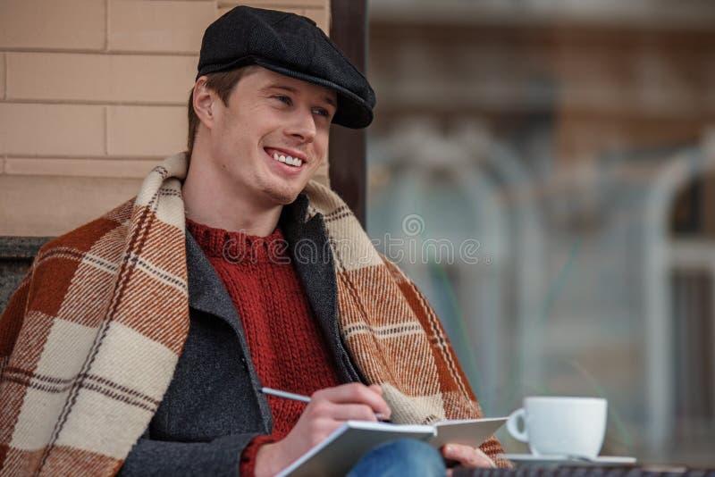 Het glimlachen mens het schrijven verhaal met koffie royalty-vrije stock afbeeldingen