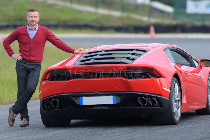 Het glimlachen mens het stellen tegen rode sportwagen op kring stock foto's