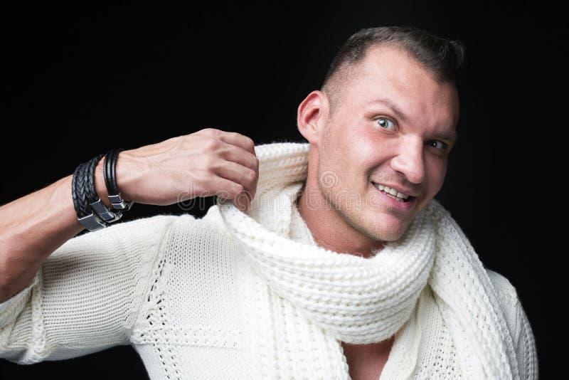 Het glimlachen mensen dicht omhoog portret van een mens in sweater en sjaal tegen donkere achtergrond royalty-vrije stock foto's