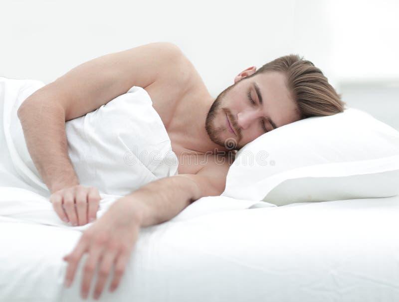 Het glimlachen mensenslaap op een comfortabel bed royalty-vrije stock foto