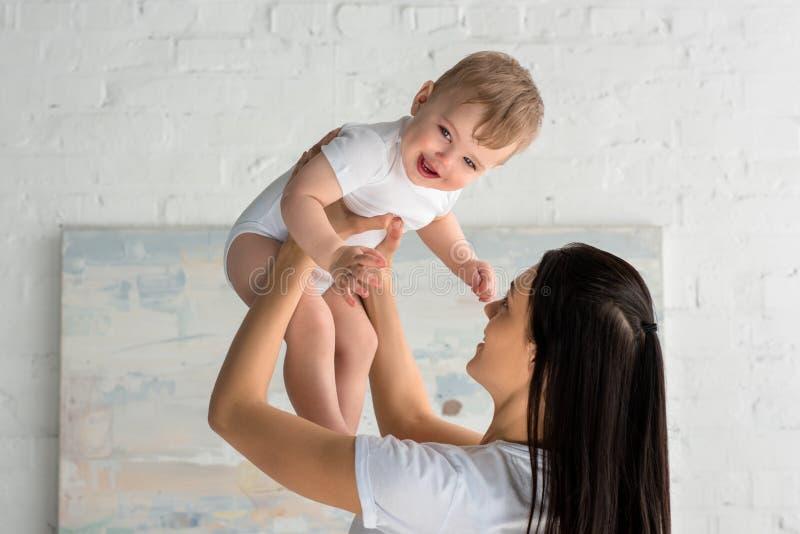 het glimlachen moeder het spelen met leuke gelukkige baby in handen stock fotografie