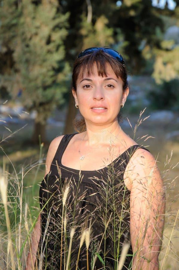 Het glimlachen mooi brunette in een bos stock fotografie