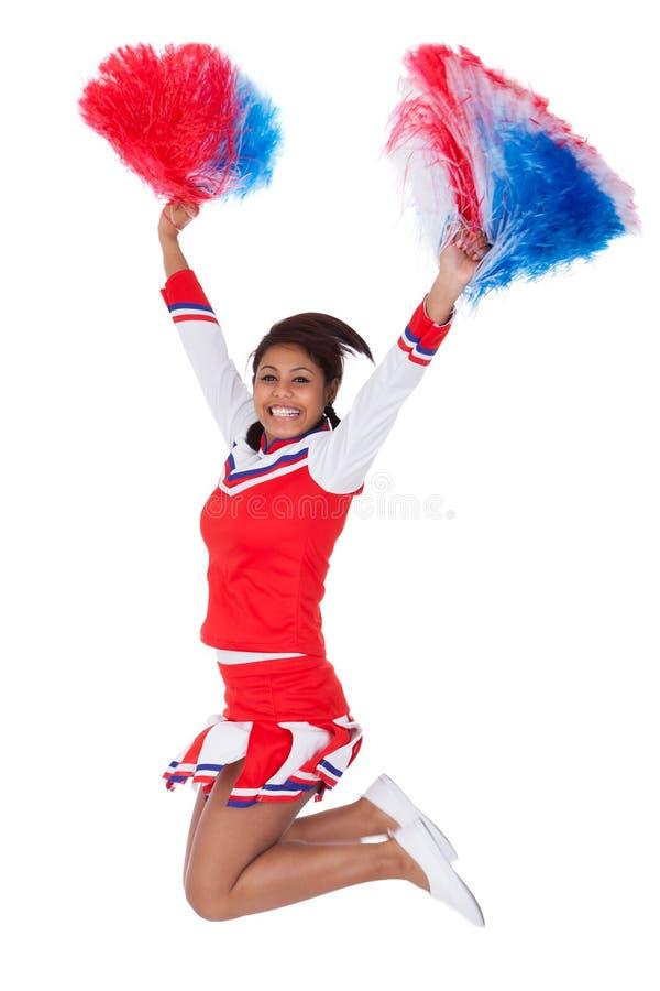 Het glimlachen mooie cheerleader met pompoms stock afbeeldingen