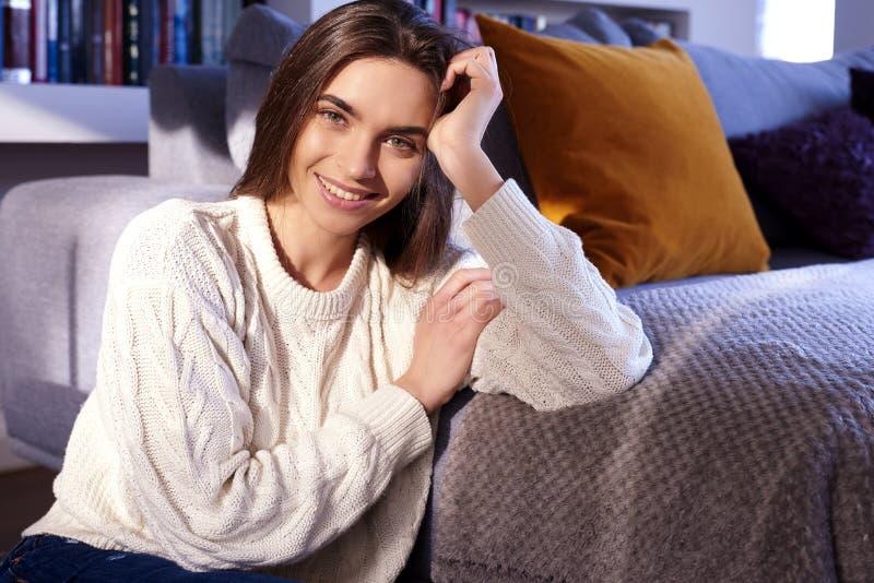 Het glimlachen het mooie jonge vrouw ontspannen op laag thuis stock foto's