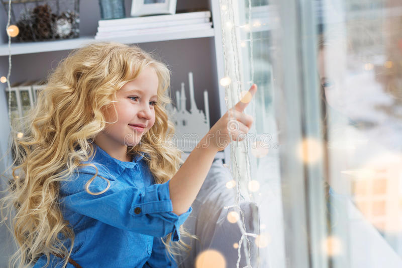 Het glimlachen mooie meisjeaanrakingen aan het venster royalty-vrije stock foto's