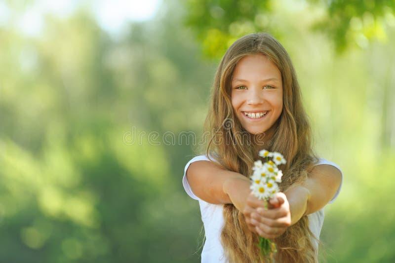 Het glimlachen mooie tiener met boeket van madeliefjes stock foto