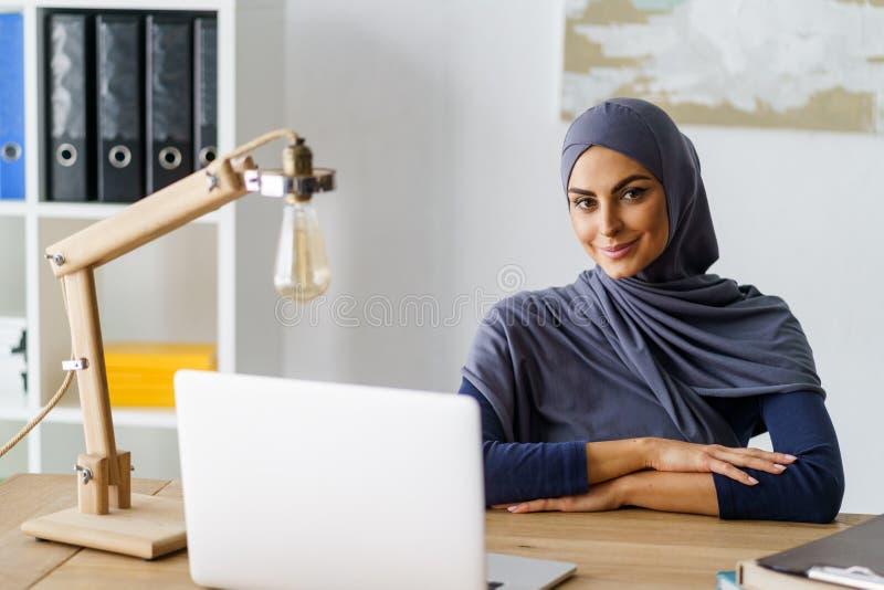 Het glimlachen moslimdamezitting stock foto's