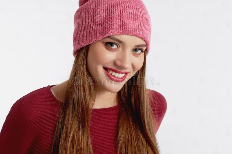 Het glimlachen omhoog maakt het aantrekkelijke vrouwelijke model in rode hoed en met stock fotografie