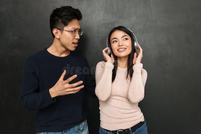 Het glimlachen onbezorgde Aziatische vrouw het luisteren muziek door hoofdtelefoons royalty-vrije stock afbeeldingen
