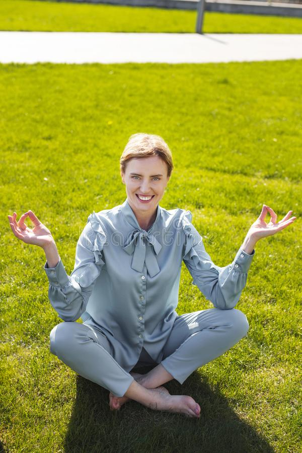 Het glimlachen het onderneemstergevoel verlichtte terwijl het zitten op het gras royalty-vrije stock foto's