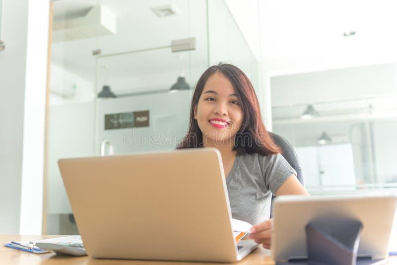 Het glimlachen onderneemsterzitting in bedrijfsbureau stock foto