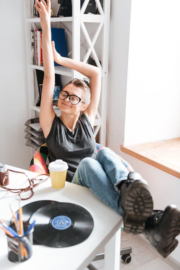 Het glimlachen ontspande zich jonge vrouw zitting en het uitrekken bij de lijst stock foto
