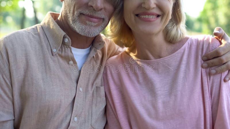 Het glimlachen het oude paar koesteren, die voor camera, welzijnsgeluk, affectie stellen royalty-vrije stock afbeelding