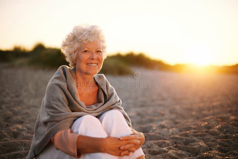 Het glimlachen oude vrouwenzitting op het strand stock afbeeldingen