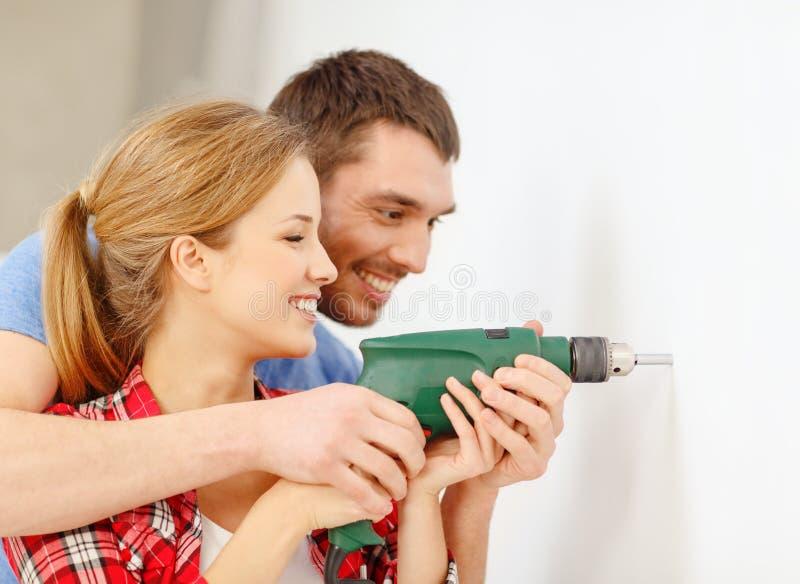 Het glimlachen paar boorgat in muur thuis royalty-vrije stock foto's