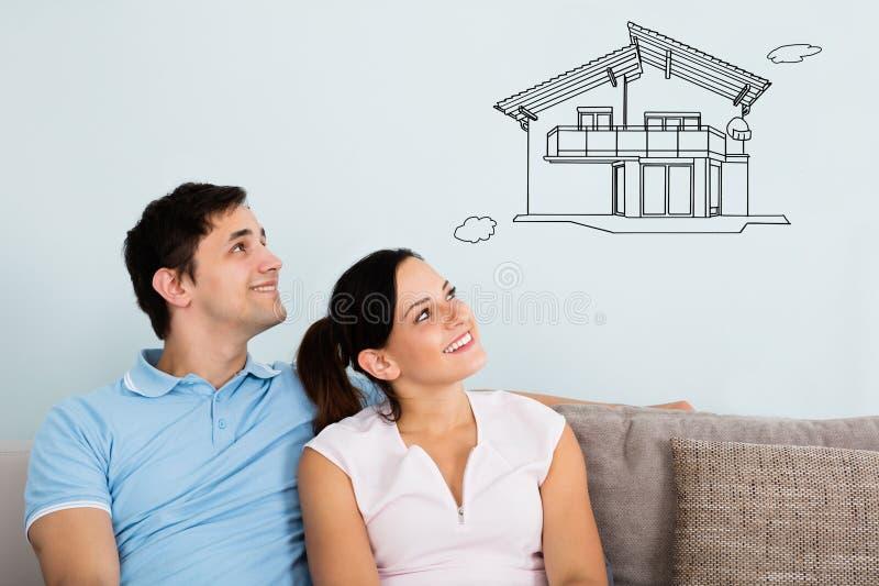 Het glimlachen Paar het Denken aan het Krijgen van Hun Nieuw Huis royalty-vrije stock afbeeldingen