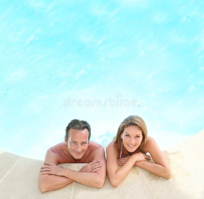 Het glimlachen paar het stellen in het zwembad royalty-vrije stock afbeeldingen