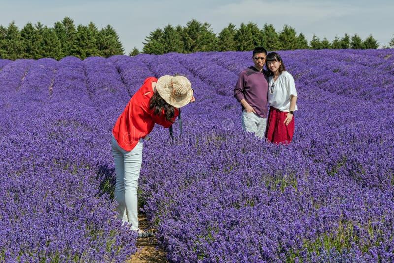 Het glimlachen paar het stellen op Lavendelgebied, Worcestershire, Engeland stock afbeelding
