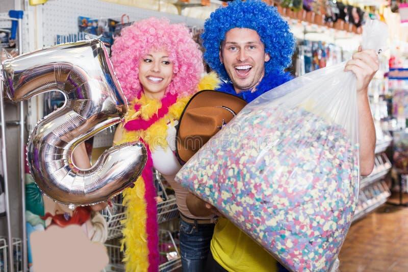 Het glimlachen paar met grote zak confettien in opslag stock afbeeldingen