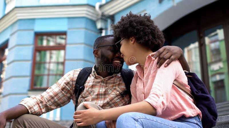 Het glimlachen paar het nuzzling, hebbend rust op straattreden, die van tijd samen genieten royalty-vrije stock foto