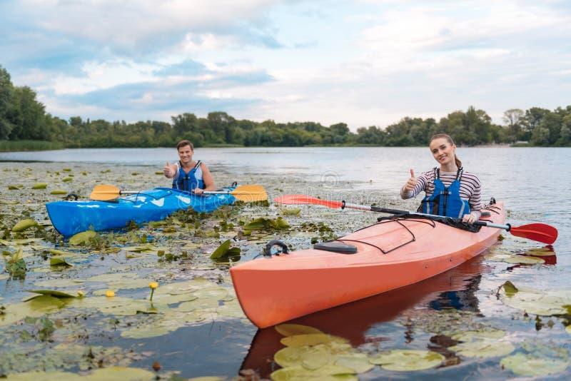 Het glimlachen het paargevoel stelde na actieve rivierrit tevreden in kano royalty-vrije stock foto's