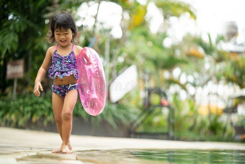 Het glimlachen peutermeisje het spelen in zwembad stock afbeelding