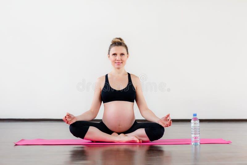 Het glimlachen plaatst de zwangere vrouwenzitting in lotos in gymnastiek met plastic waterfles stock fotografie