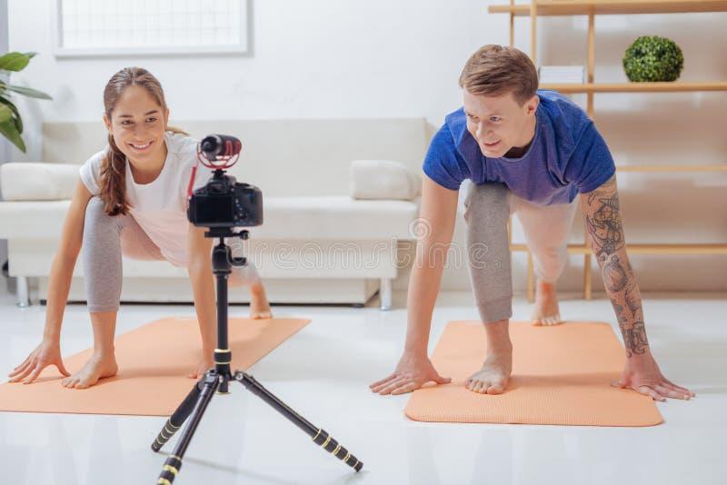 Het glimlachen positieve bloggers die oefeningen voor een camera doen stock foto's